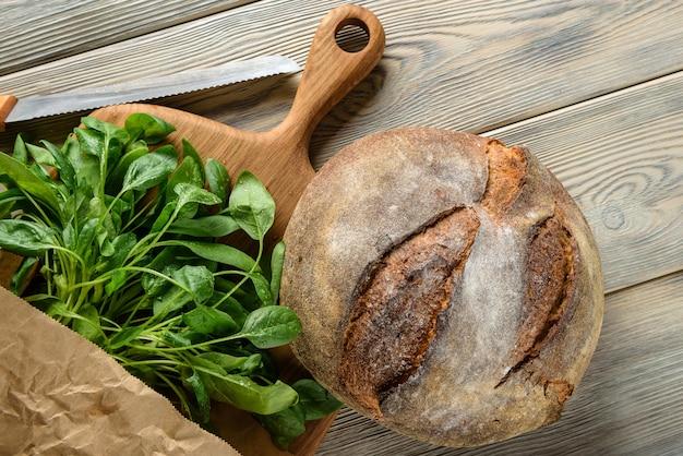 Platliggende compositie met een brood van donker zelfgebakken brood en spinazie.