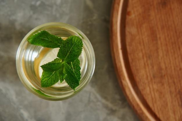 Platliggende compositie met gezonde munt-citroendrank met muntblaadjes en gesneden citroen in een glas naast een gesneden ronde houten plank op een grijs keukenoppervlak.