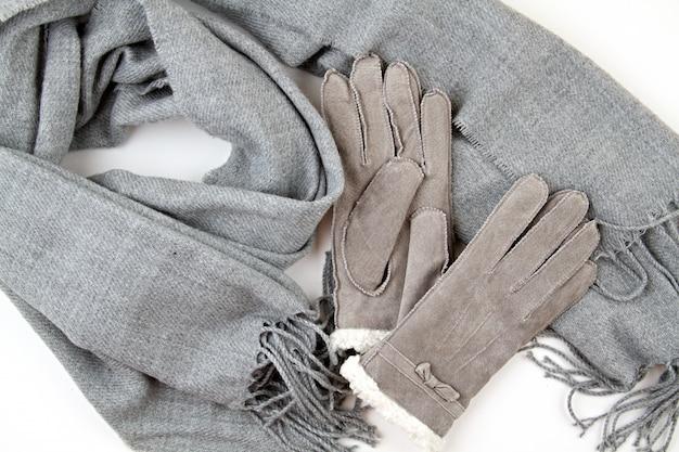Platliggende compositie met grijze winterhandschoenen en een warme wollen sjaal