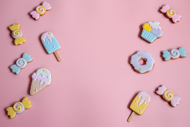 Platliggende compositie met heldere geglazuurde peperkoekkoekjes op roze achtergrondkopieerruimte.