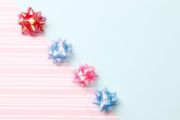 Platliggende compositie met kronkelige strik op een roze en blauwe achtergrond met ruimte voor tekst.