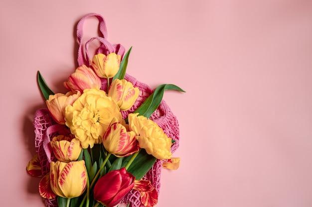 Platliggende compositie met lentebloemen op de kopieerruimte van de stringtas.