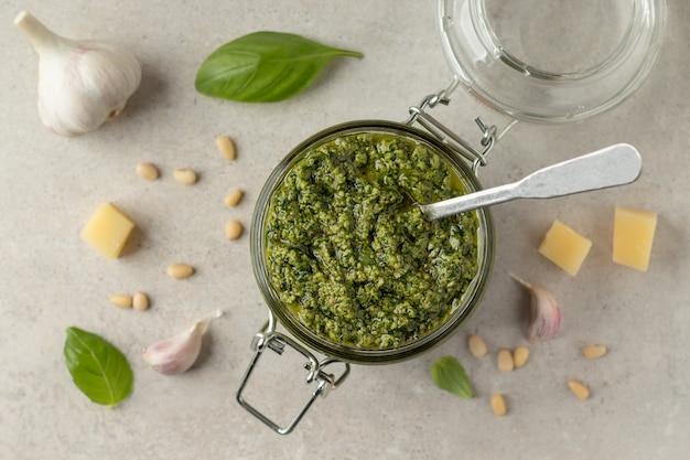 Platliggende compositie met pot groene pestosaus en ingrediënten op grijze tafel