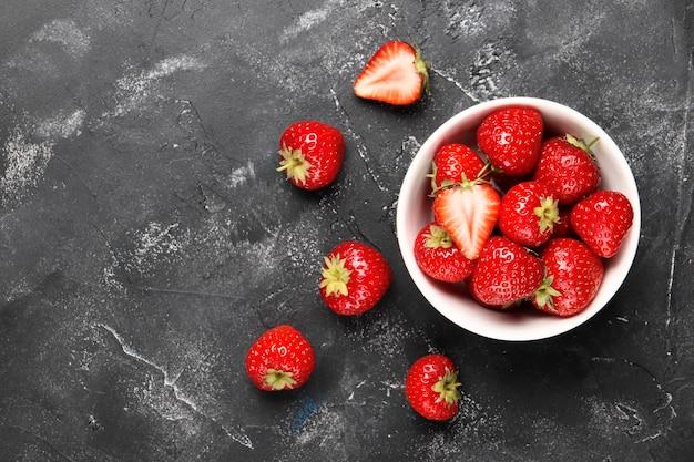 Platliggende compositie met rijpe rode aardbeien op zwarte achtergrond