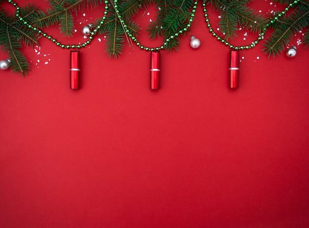 Platliggende compositie met rode lippenstift in de vorm van kerstverlichting schoonheidsbanner kopieerruimte