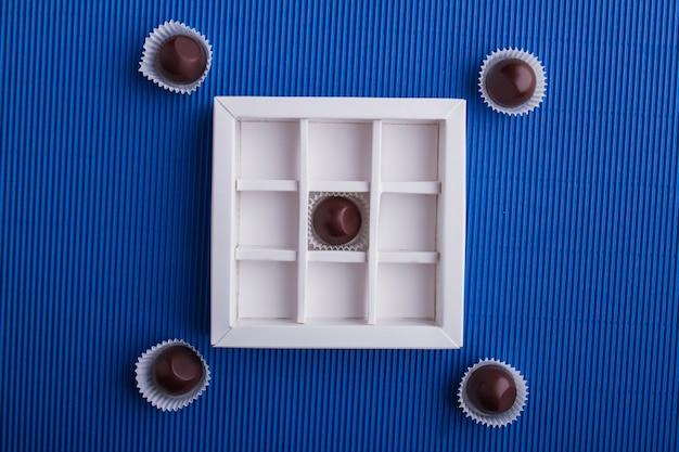 Platliggende compositie van donkere chocolaatjes met de doos