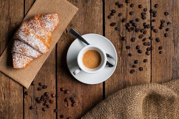Platliggende espresso met croissant en koffiezaden
