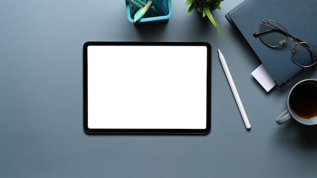 Platliggende foto van mock-up digitale tablet met leeg scherm op grijze tafel. leeg scherm voor tekstbericht of informatie-inhoud.