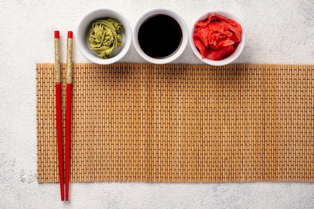Platliggende gemberwasabi en sojasauskommen met tafelkleed