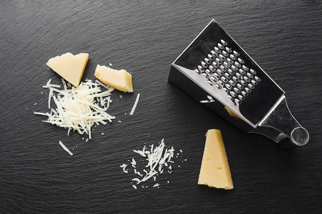 Platliggende geraspte parmezaanse kaas met rasp