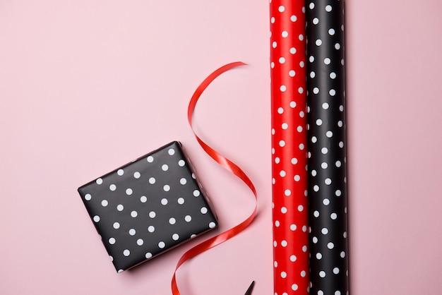 Platliggende geschenkdoos en verjaardagsdecoraties cadeau op roze.