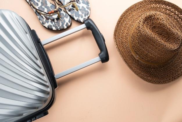 Platliggende grijze koffer met bruine hoed en sandalen
