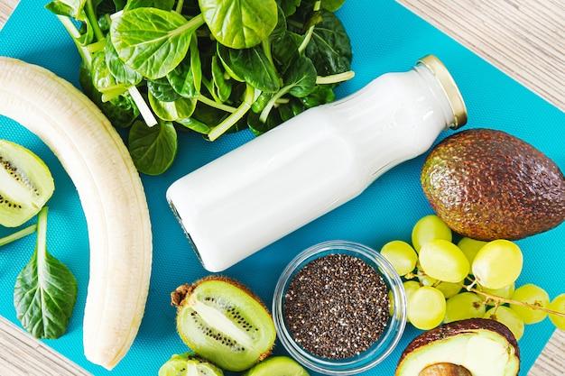 Platliggende ingrediënten voor een groene smoothie. bovenaanzicht op een turquoise achtergrond van banaan, spinazie, chiazaden, kokosmelk in een glazen pot, avocado, druiven. detox, smoothie recept voor een gezond voedingspatroon.