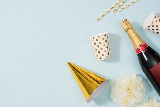 Platliggende kerst- of feestachtergrond met geschenkdozen, champagnefles, strikken, decoraties en inpakpapier in goud. platliggend, bovenaanzicht