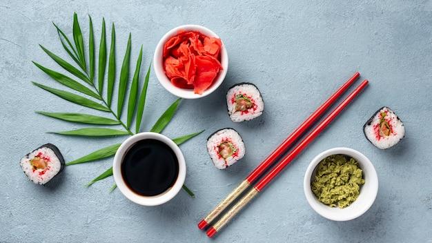 Platliggende maki-sushi rolt eetstokjes en sojasaus