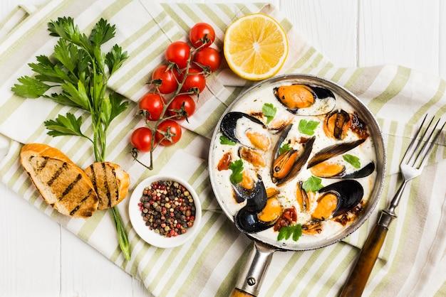 Platliggende mosselen in witte saus en zijden op tafelkleed