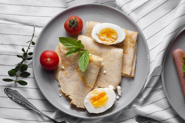 Platliggende pannenkoeken met hardgekookte eieren en tomaten