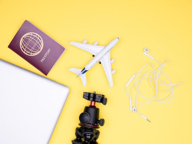 Platliggende reizigersaccessoires op gele achtergrond, met paspoort en laptop