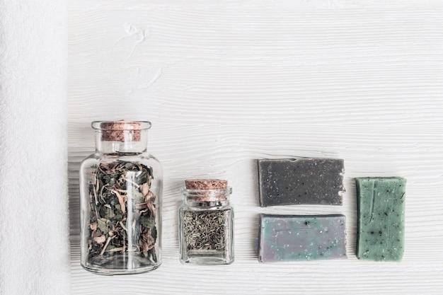 Platliggende samenstelling met cosmetische producten voor de badkamer, natuurlijke zeep met geurende additieven, witte handdoek, kleine glazen potten met organische kruiden. spa, aromatherapie en lichaamsverzorging behandeling concept.