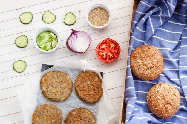 Platliggende veggie quinoa burger met tomaat, ui, komkommer, sla en burgerbrood