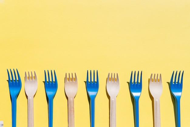Platliggende vergelijking tussen wegwerpbestek van bamboe en plastic bestek. herbruikbare en houten vorken. recycling, milieuvriendelijk, afvalvrij concept, plasticvrije alternatieven voor milieubescherming
