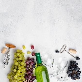 Platliggende wijnflessen druiven met kurkentrekker