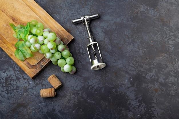 Platliggende wijnopener met groene druiven