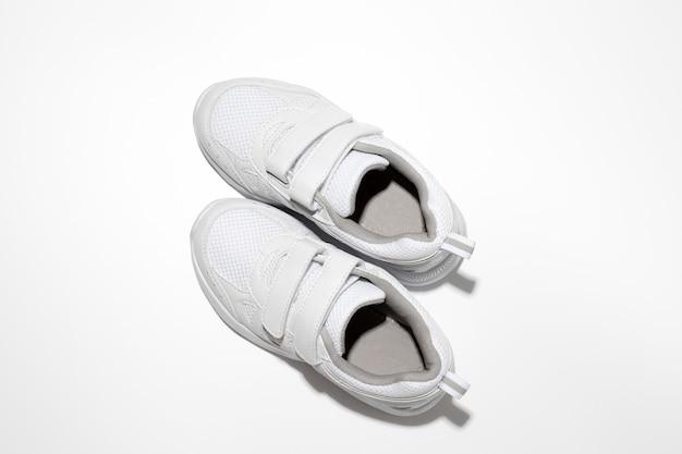 Platliggende witte sneakers met klittenbandsluitingen voor zwangere vrouwen of mensen met een handicap isoleren...