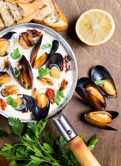 Platronde pan met mosselen in witte saus