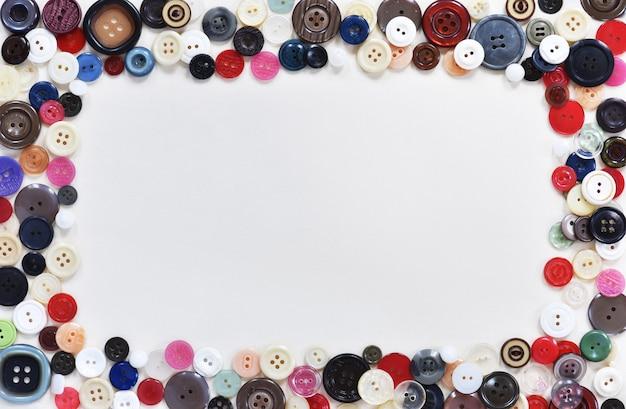 Platte compositie met knoppen en naai benodigdheden op witte achtergrond