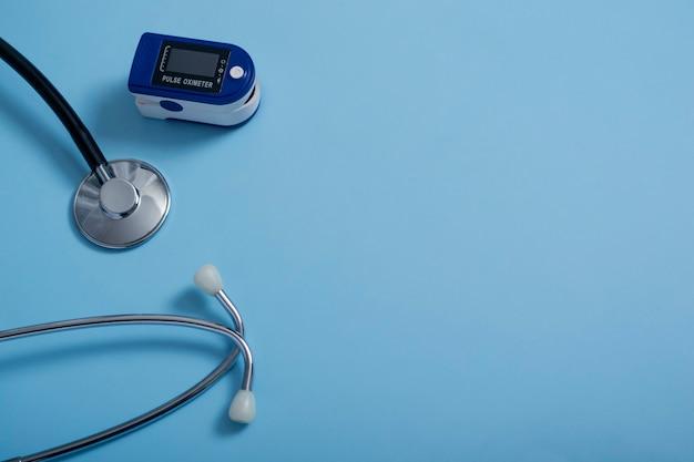 Platte compositie met pulsoximeter en stethoscoop op blauwe achtergrond. een pulsoximeter die wordt gebruikt om de hartslag en zuurstofniveaus te meten.