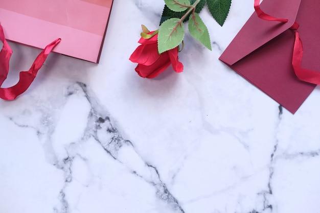Platte compositie van roos, envelop en cadeau op tegel achtergrond