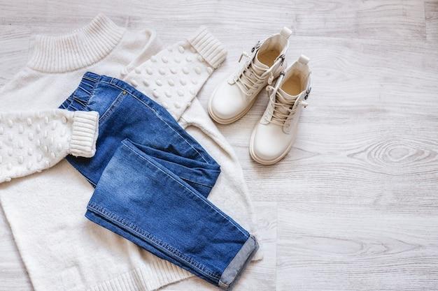 Platte herfstkleding voor dames met een warme witte trui, spijkerbroek en witte schoenen kopieer ruimte