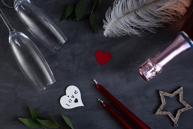 Platte lay compositie met fles champagne, kaarsen, veren en harten voor viering op grijze betonnen achtergrond. glas voor champagne.