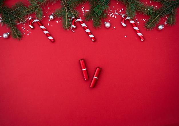 Platte lay compositie met rode lippenstift en kerstdecor op rode achtergrond bovenaanzicht beauty banner