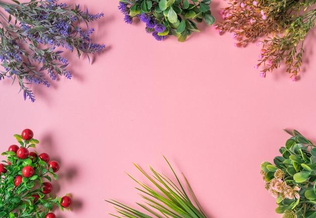 Platte lay-out van gedroogde bloemtakken op een roze achtergrond, bovenaanzicht, kopieerruimte.