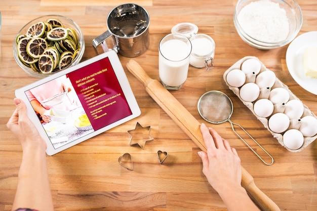 Platte lay-out van handen van jonge huisvrouw met tablet en deegroller terwijl thuis gebak gaat koken