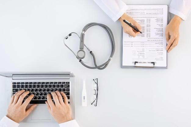 Platte lay-out van handen van verpleegster met pen medische geschiedenis formulier in te vullen zittend door bureau voor collega met laptop op werkplek