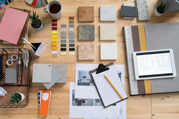 Platte lay-out van verschillende dingen voor het werk van een hedendaagse interieurontwerper - voorbeelden van behang en panelen, elektronische schetsen en anderen