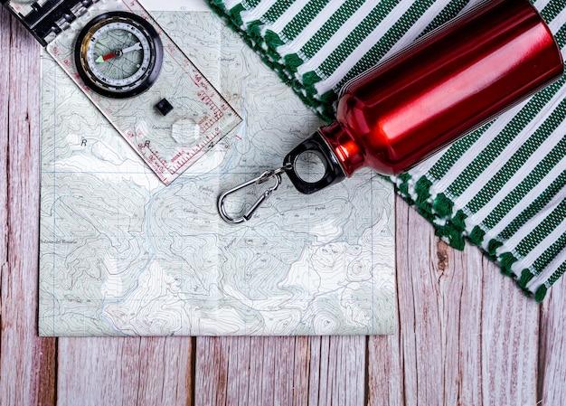 Platte lay-out van wandeluitrusting - kaart, fles en kompas