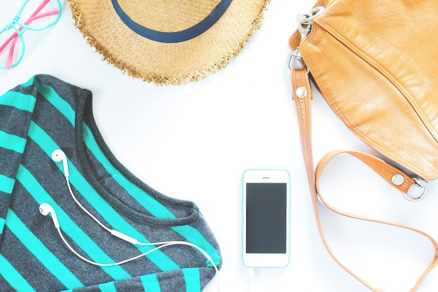 Platte lay vrouwelijke kleding en accessoires collage met t-shirt, modebril, hoed met mobiele telefoon en oortelefoon op witte achtergrond.