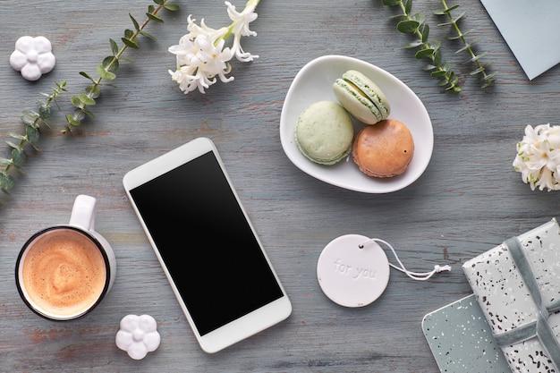 Platte lentelok met bloemen van parelhyacint, eucalyptus, mobiele telefoon en kaarten