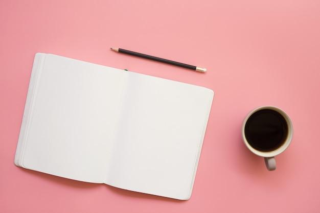 Platte ontwerp van werkruimte bureau met lege notebook potlood en koffie op vintage pastel kleur achtergrond.