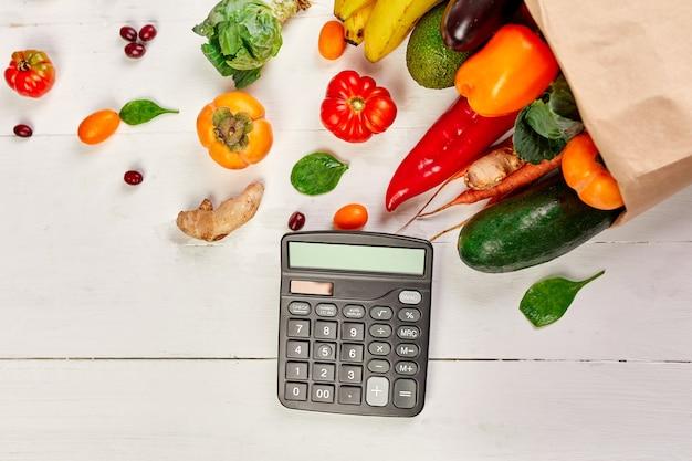 Platte papieren boodschappentas met assortiment van verse groenten en fruit en rekenmachine, bio-gezond, biologisch voedsel op witte achtergrond, supermarktstijl, kruidenierswinkel, dieet vegetarisch voedsel.