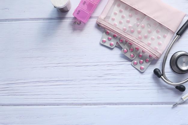 Platte samenstelling van stethoscoop en pillen op houten achtergrond.