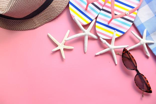 Platte samenstelling van zomer strand accessoires op roze achtergrond.