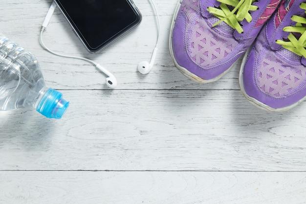 Platte sportschoenen, smartphone en fitnessapparatuur.