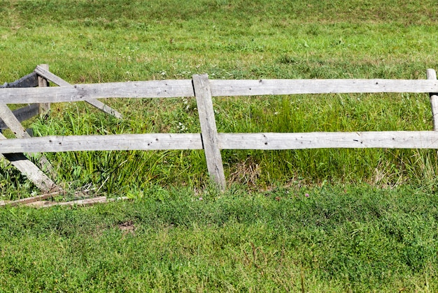 Platteland en veld waarvan het grondgebied is gescheiden door een eenvoudig houten hek, close-up