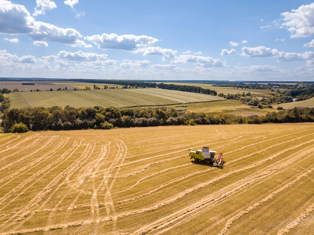 Platteland landschap luchtfoto van drone tot landbouwgebied met combineren op een blauwe hemel