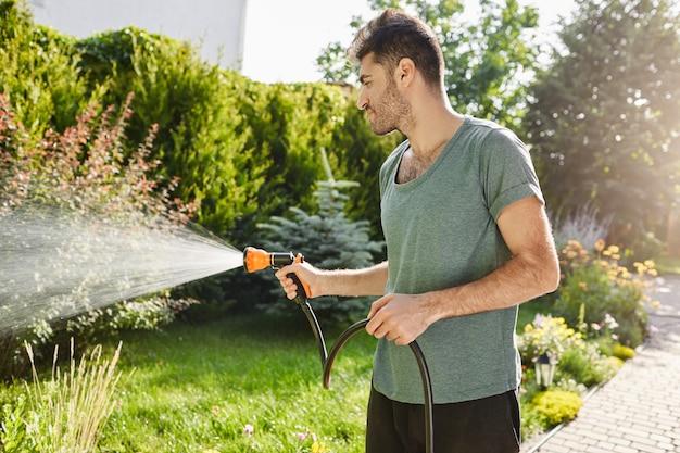 Platteland levensstijl. buiten portret van jonge knappe tuinman tijd doorbrengen in plattelandshuis, planten water geven met gieter, ontspannende tijd hebben.